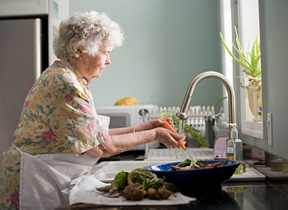 Elderly woman washing carrots