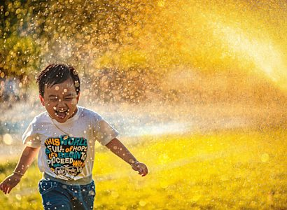 Little Boy Smiling And Running As Water Falls On Him Edited