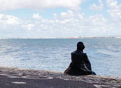 Muslim woman sitting by coast