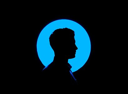 Silhoutte of man infront of blue circle