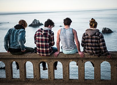Four young people sitting on bridge